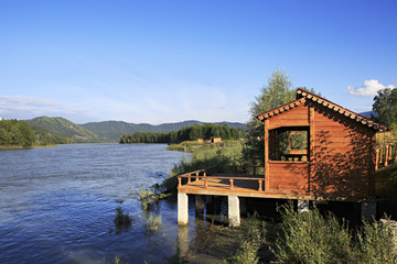 Wooden veranda on the mountain river Katun.