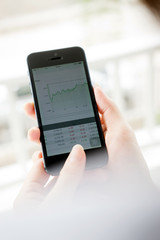 Women analyse stock market using mobile smart phone