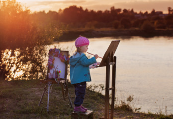 child draws a picture outdoor