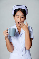 Young Asian nurse yawn with a cup of coffee