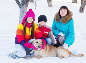 family with dog in a snowy garden