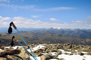 Trekking poles on a snowy summit of a mountain with a great view