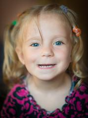 Cute little girl smiling over dark background.