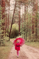little girl with umbrella in forest