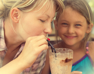 mother and daughter drinking chocolate cocktail in cafe