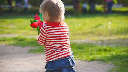 little girl walks in the park with a toy
