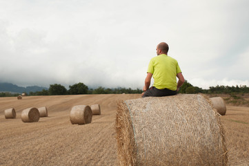 Young man in a field with straw bales. Resting on a bale