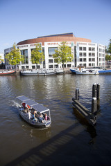 small boat in river amstel in front of opera house