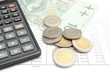 Heap of coins, paper money and calculator on spreadsheet