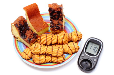 Fresh baked pastry and glucose meter. White background