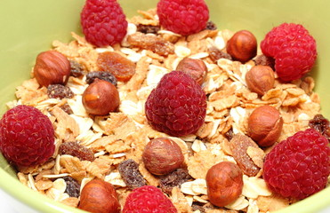 Heap of muesli with hazelnut and raspberries in green bowl