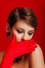 Beautiful girl in red gloves and jewelry