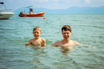 Father and son swimming in ocean water with sailboats at