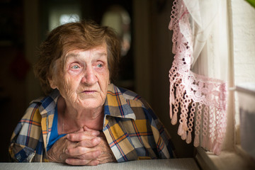 Old woman sitting at a table in his house