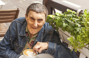 Elderly disabled man with cerebral palsy, sitting at an cafe.