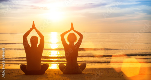Yoga silhouette of a young couple on the beach at sunset. - 69806618