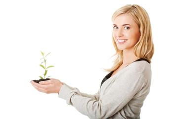 Woman with plant and dirt in hand