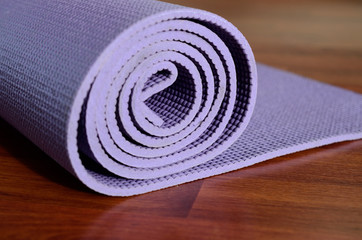 Yoga mat on wooden background