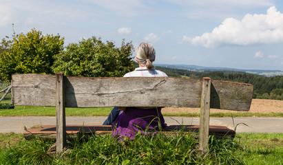 Rentnerin macht Rast auf einer Bank in der Natur
