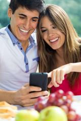 Couple using smart phone on romantic picinic.