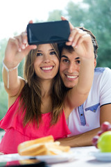 Couple taking photo of themselves with smart phone on romantic p