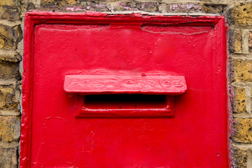 a traditional red post box in a wall.