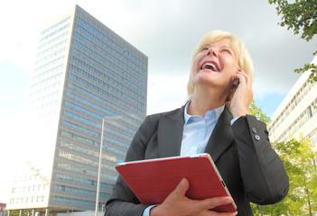 Geschaeftsfrau lachend mit Handy und Blick in den Himmel