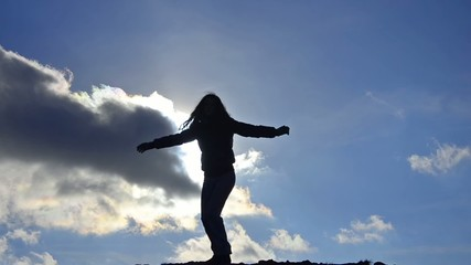 Silhouette of girl on the bright sky, Freedom concept