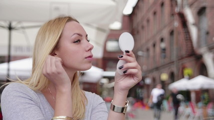 Young attractive woman applying make up outdoors