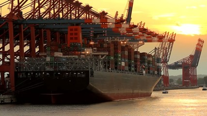 Container ship loading and unloading at sunset