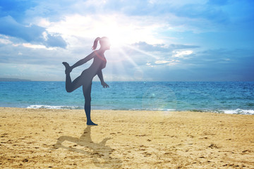 Silhouette of a woman stretching her leg on the beach