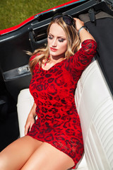 Sexy blonde woman laying in cabriolet