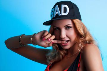 Portrait of sexual seductive female in black hat on blue backgro