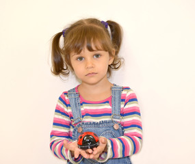 Portrait of the little girl with a toy in hands on a light backg