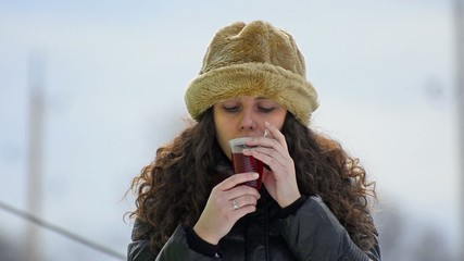 gorgeous teen with fur hat drinking hot tea on skislope