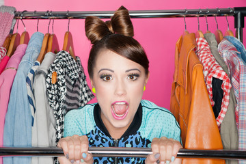 Young attractive woman with clothes rack