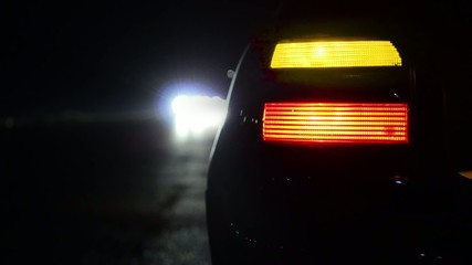 Flashing orange blinker light on car parked on side at night