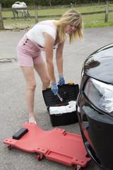 DIY car maintenance Woman driver with crawler