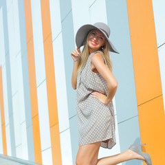 beautiful happy girl in a bright dress and a long hollow hat