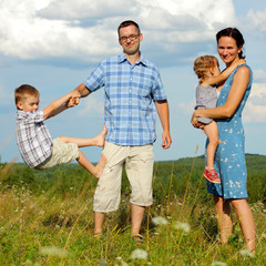 happy young family of four having fun on the top of a hill