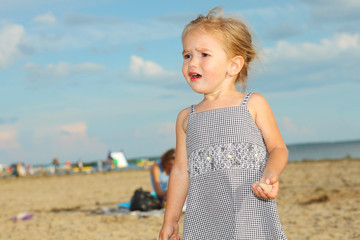 offended crying little girl on the beach.