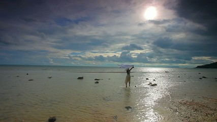 Happy young woman run to the sun with veil on beach in Koh Samui