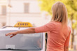 woman raising her arm to call a taxi