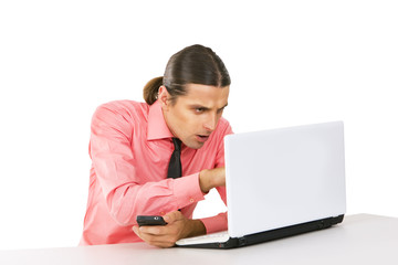 Young man with laptop looking at the monitor over white backgrou