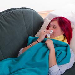 Krank auf der Couch liegen und Nase putzen