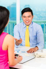 Asian advisor with client on financial investment