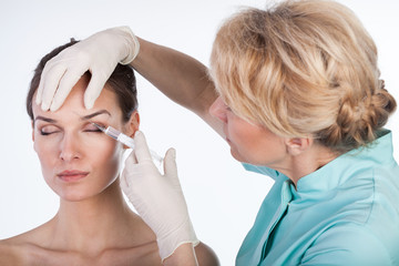 Doctor injecting botox in the forehead