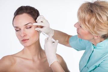 Injecting botox on isolated white background