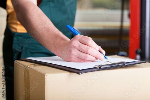 canvas print picture Man's hand signing delivery document