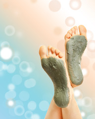 Woman foots with cosmetic clay on bright background